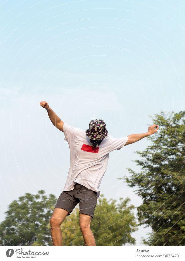 Ein junger Erwachsener, der eine Schutzmaske trägt, um eine Infektion mit dem Coronavirus zu vermeiden, während er einen Ollie-Stunt auf seinem Skateboard im Freien auf einer leeren Straße macht.