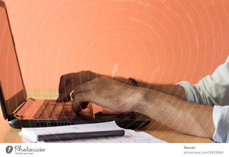 Nahaufnahme der Hände eines jungen Erwachsenen, der von zu Hause aus auf einem Laptop arbeitet. Arbeit von zu Hause aus Aufenthalt in Arbeitswohnung