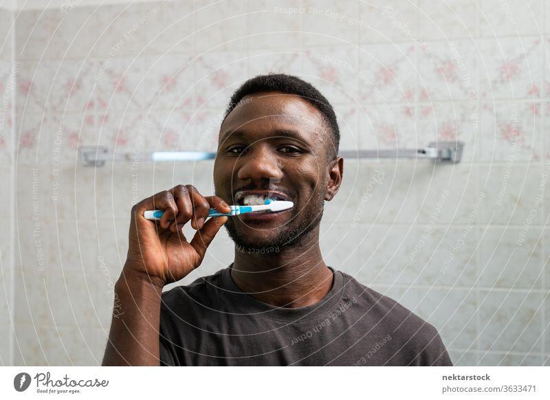 Junger schwarzer Mann putzt gründlich seine Zähne Zähneputzen Zahnbürste 1 Mensch afrikanische ethnische Zugehörigkeit Pflege Zahncreme in die Kamera schauen