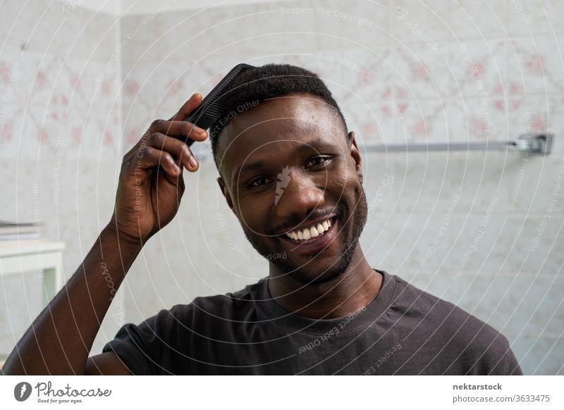Gutaussehender schwarzer Mann lächelt und kämmt Haare im Badezimmer Kamm Kämmen Behaarung Gesicht Frisur 1 Mensch afrikanische ethnische Zugehörigkeit Lächeln