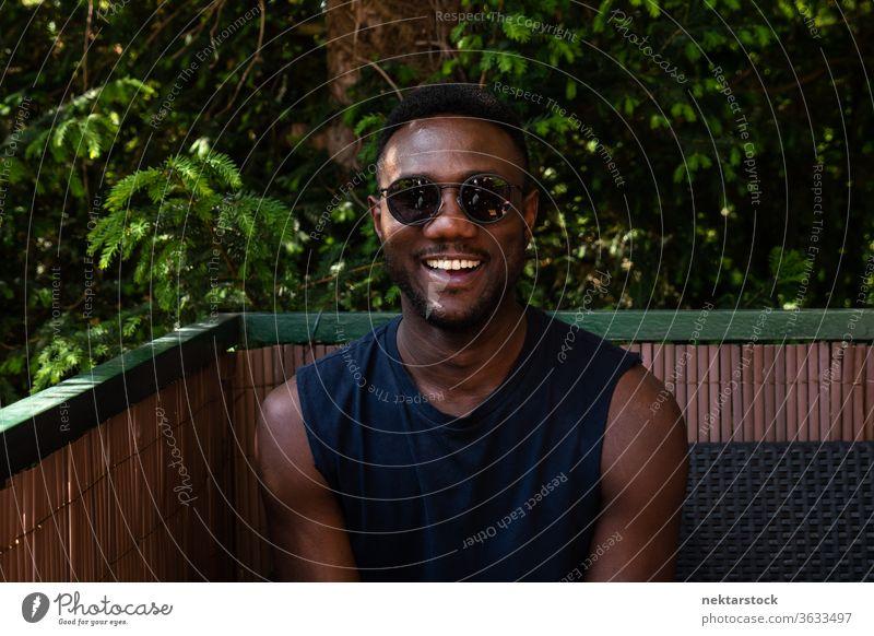 Junger schwarzer Mann lächelt vor der Kamera im Freien 1 Mensch afrikanische ethnische Zugehörigkeit Sonnenbrille Lifestyle in die Kamera schauen Terrasse