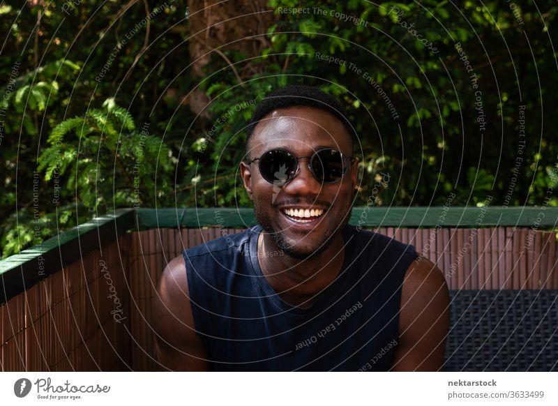 Junger schwarzer Mann zur Kamera im Freien 1 Mensch afrikanische ethnische Zugehörigkeit Sonnenbrille Lifestyle in die Kamera schauen Terrasse Balkon Sommer