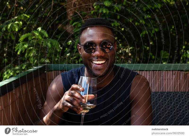 Schöner schwarzer Mann mit einer Tasse Wein in der Hand lächelt weit draussen 1 Mensch afrikanische ethnische Zugehörigkeit Sonnenbrille Weißwein Beteiligung
