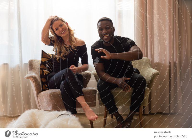 Porträt eines gemischten Rennpaares in Sesseln sitzend und vor der Kamera lächelnd Lifestyle Paar 2 Menschen Lächeln männlich Frau gemischtrassiges Paar winkend