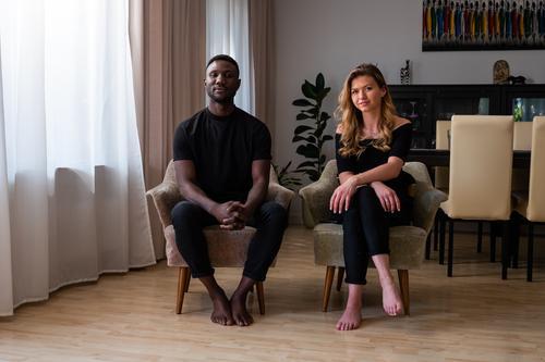 Porträt eines gemischtrassigen Paares in Wohnzimmersesseln sitzend Lifestyle 2 Menschen männlich Frau gemischtrassiges Paar reales Leben echte Menschen