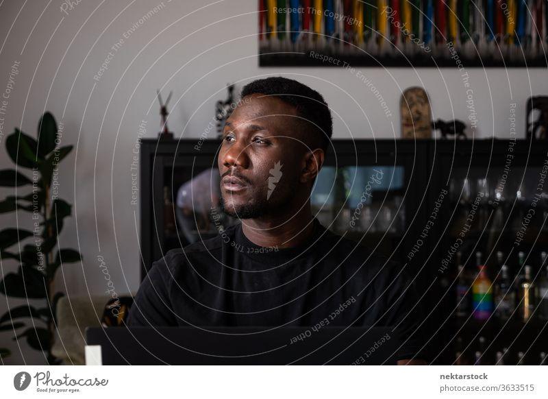 Porträt eines gut aussehenden schwarzen Mannes, der im Wohnzimmer sitzt und wegschaut 1 Mensch afrikanische ethnische Zugehörigkeit Lifestyle 20-30 Jahre alt