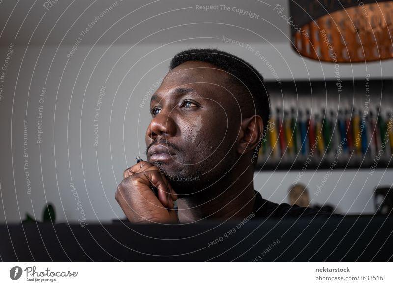 Porträt eines schwarzen Mannes, der mit der Hand auf dem Kinn denkt 1 Mensch Hand am Kinn afrikanische ethnische Zugehörigkeit Lifestyle 20-30 Jahre alt