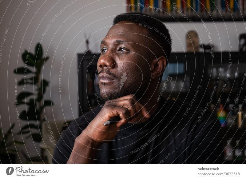 Porträt eines Schwarzen, der im Wohnzimmer denkt Mann 1 Mensch Hand am Kinn afrikanische ethnische Zugehörigkeit Lifestyle 20-30 Jahre alt gutaussehend