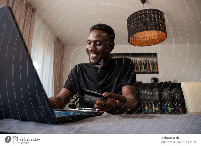 Junger schwarzer Mann lächelt beim Online-Einkauf vom Wohnzimmer aus online Kreditkarte Online-Shopping Bankkarte Lächeln Fröhlichkeit positive Emotion Kauf