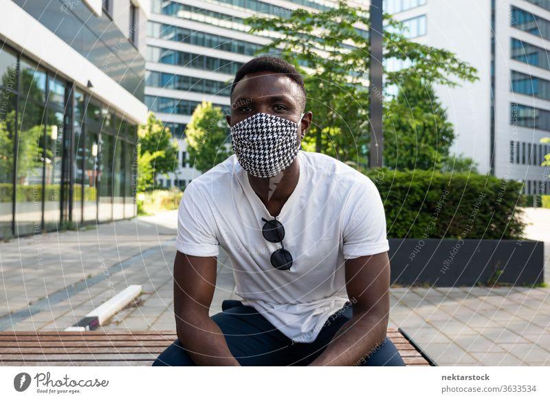 Junger schwarzer Mann mit Gesichtsmaske, der in die Kamera schaut Mundschutz 1 Mensch afrikanische ethnische Zugehörigkeit Lifestyle in die Kamera schauen Bank