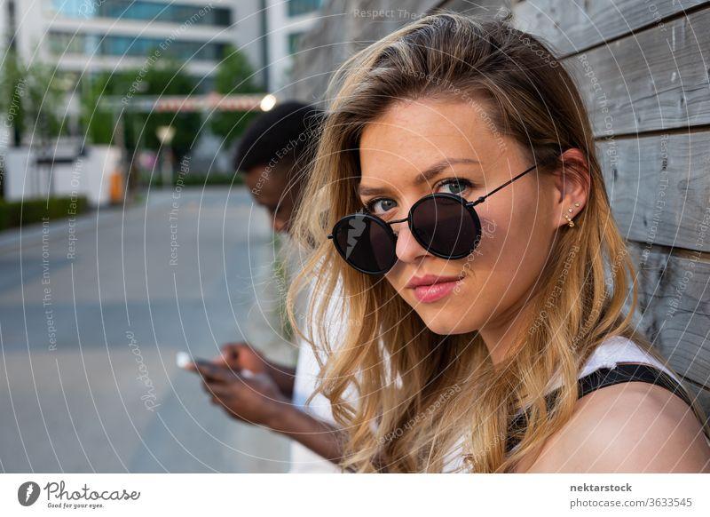 Junge Frau mit runder Sonnenbrille schaut in die Kamera Porträt verschwommener Hintergrund Mann Smartphone Lifestyle in die Kamera schauen 2 Menschen männlich