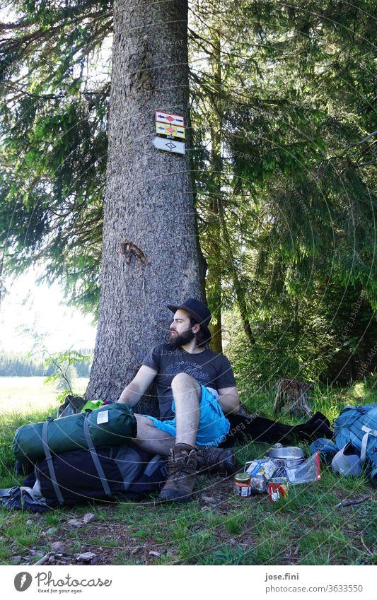 Der Mann sitzt an den Baum gelehnt und macht eine Pause vom Wandern, währenddessen überlegt er, was für ein weiter Weg noch vor ihm liegt mit seinem schweren Rucksack.