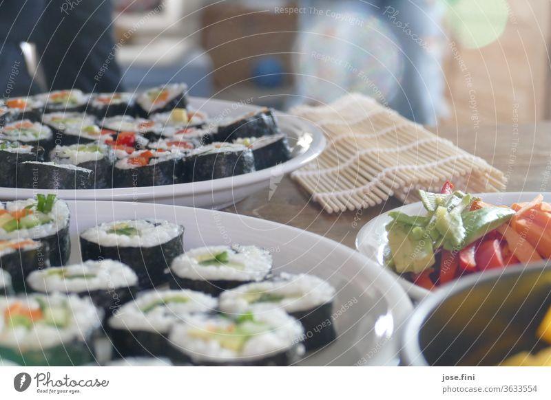selbstgemachtes vegetarisches Sushi mit verschiedenem Gemüse und Sushimatte im Hintergrund Gericht Essen zubereiten hausgemacht Ernährung Mahlzeit