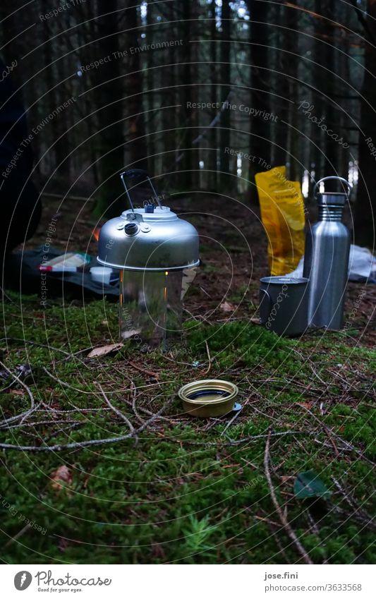 Spiritusbrenner mit Aluminium-Teekanne zum Wasser kochen in der Natur auf Waldboden Aluminiumbehälter Energie Proviant Nacht Abend Rucksackurlaub Outdoor