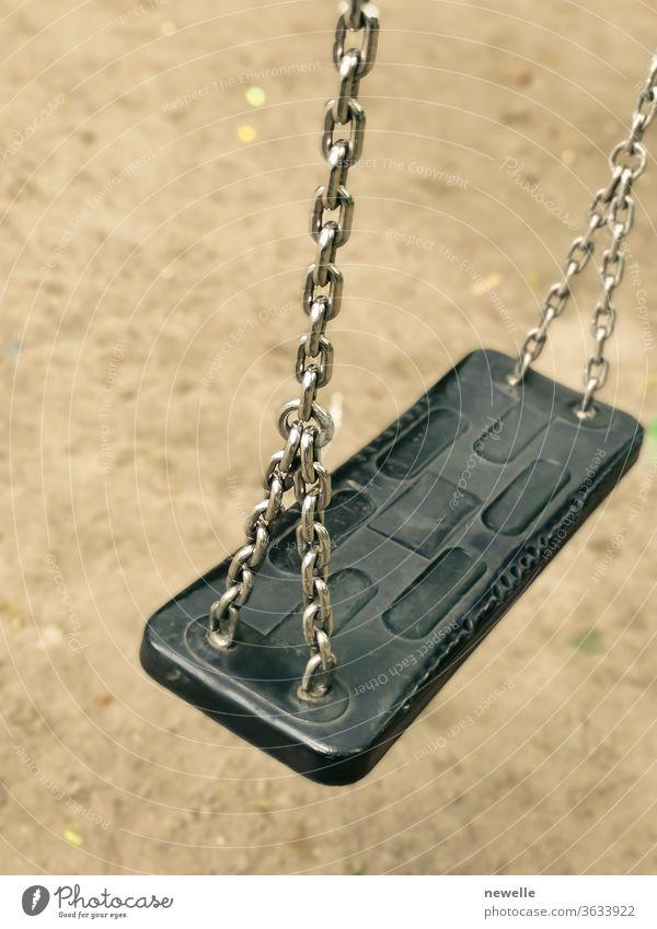 Leere Schaukel auf einem Kinderspielplatz. leere Kettenschaukel für Kinder in einem Park im Erdgeschoss. Nahaufnahme. Coronavirus verursacht leere Spielplätze