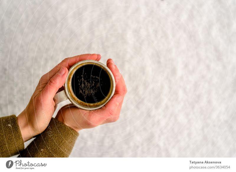 Alte Tasse mit heißem Kaffee oder Teetrinken auf Schnee im Winter Becher kalt Fäustlinge warm Weihnachten Feiertag weiß Getränk Saison im Freien außerhalb Wald
