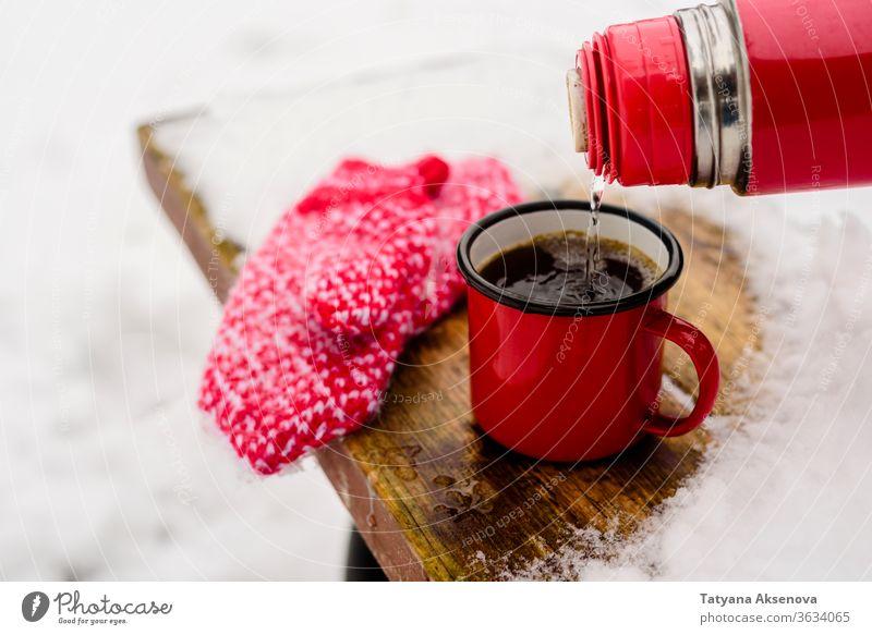 Rote Tasse mit heissem Kaffee oder Tee trinken auf Schnee im Winter heiß Becher kalt Fäustlinge rot warm Weihnachten Feiertag weiß Getränk Saison im Freien