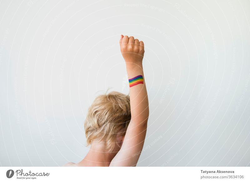 Aufgerichtete Kinderhand mit Regenbogen-Tattoo der LGBTQ-Stolzflagge Fahne lgbtq Freiheit schwul lesbisch Homosexualität Symbol Hand angehoben Rechte farbenfroh