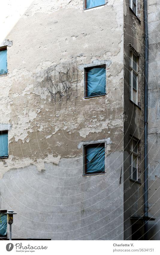 Alt | Hausfassade mit blätterndem Putz, mit blauen Planen statt Fenstern und einer Lampe hausfassade Fassade alt abblättern marode zugehängt verhängt Regenrinne