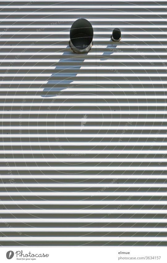 Fassade eines Zweckgebäudes aus grauem Wellblech mit zwei runden Lüftungsrohrausgängen (groß/klein) im oberen Teil, die Schatten werfen Gebäude Wellblechfassade