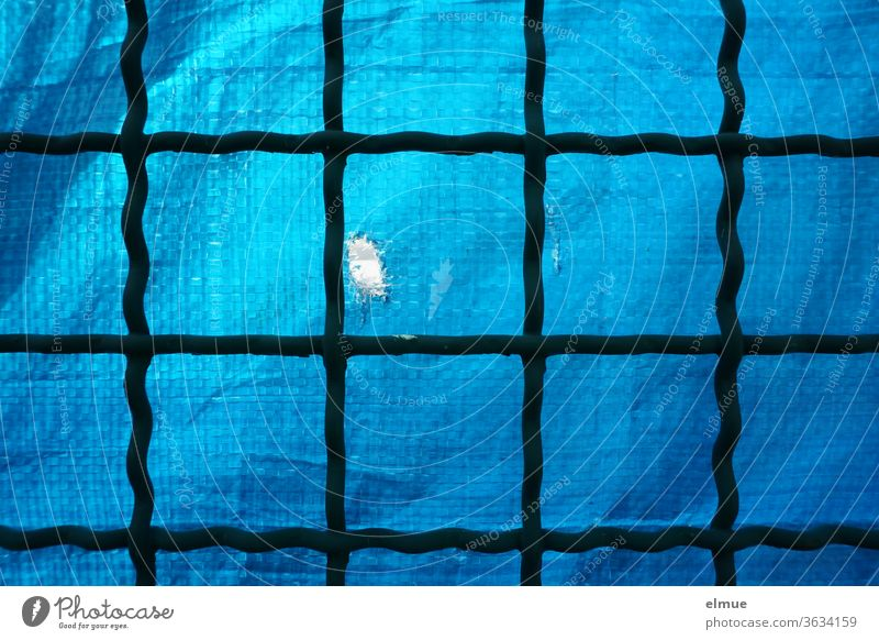 alter Gitterzaun aus Metall, hinterlegt mit blauer, derber Plastikfolie als Sichtschutz, die einen Riss als Guckloch hat Metallzaun PVC-Plane Grenze Schutz