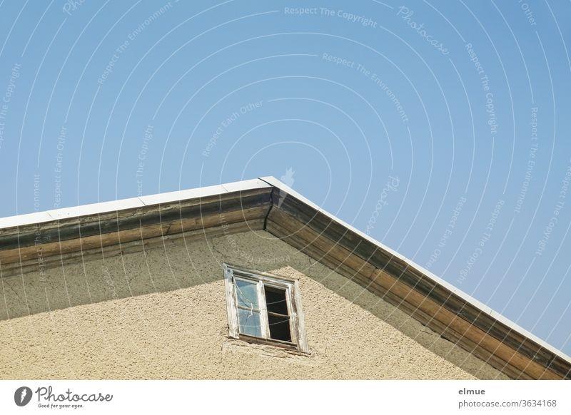 Teil eines Hausgiebels mit einem kaputten, maroden, quadratischen Holzfenster vor blauem Himmel Fenster Wand wohnen offen Glas himmelblau Fassade Ausblick
