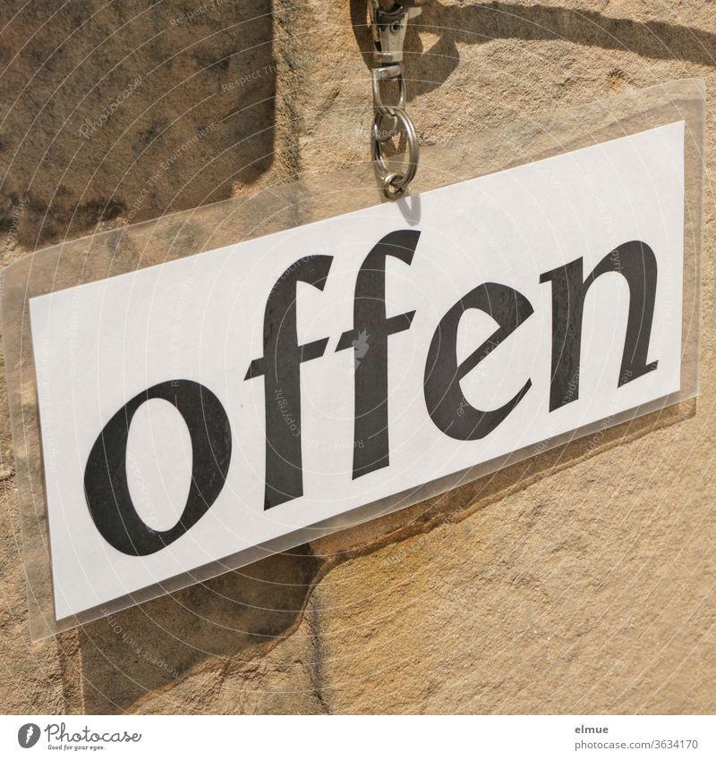 """ein laminiertes weißes Blatt Papier mit schwarzer Schrift  """"offen"""" ist mittels Metallring an einer Wand befestigt Schild geöffnet unverschlossen Einlass"""