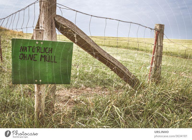 grünes Schild mit der Aufschrift NATÜRLICH OHNE MÜLL an einem Weidezaun Wiese Zaun Schilder & Markierungen Hinweisschild Schriftzeichen Typographie Satz
