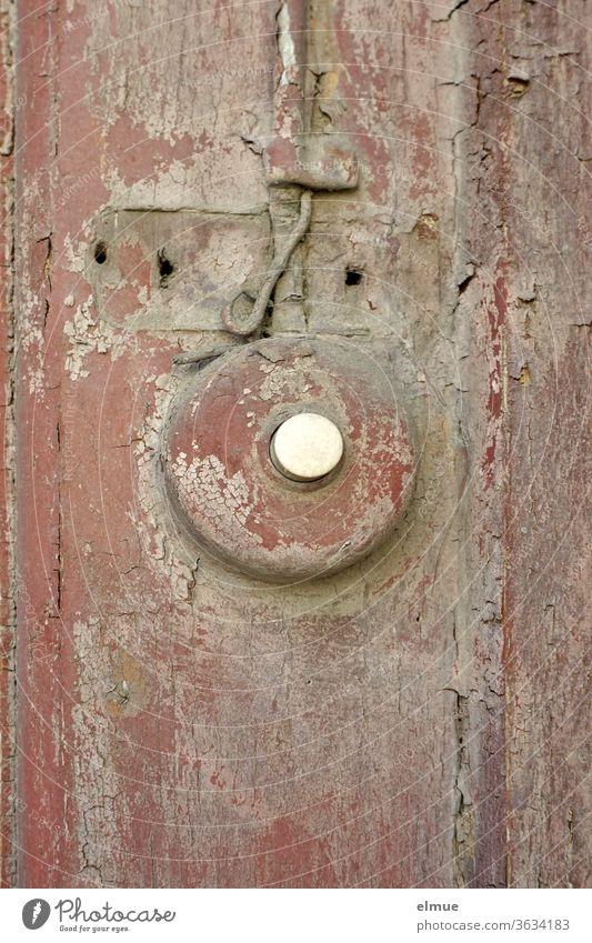 vom vor langer Zeit weinrot und später grau überstrichenen Klingelknopf blättert die Farbe ebenso ab wie vom Holz auf dem er befestigt wurde marode abblättern