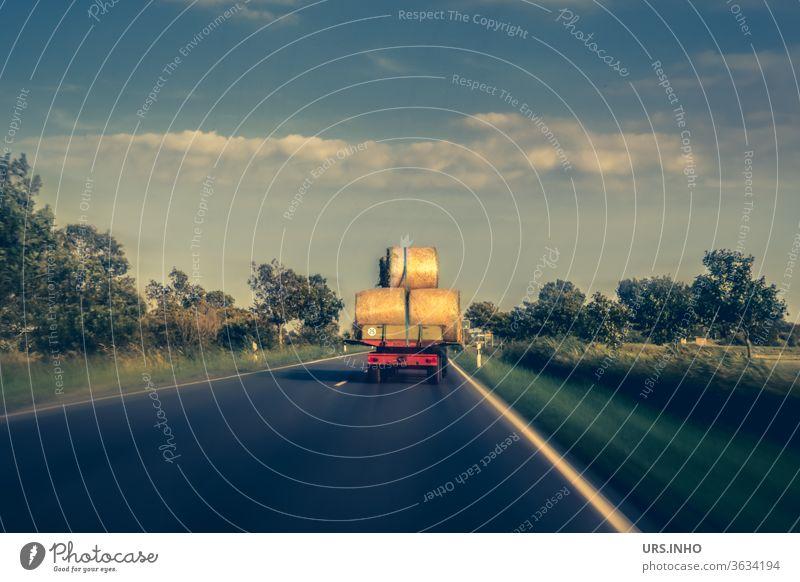 ein Traktor fährt mit Heuballen beladen auf einer Landstraße Landwirtschaft Ernte Natur wolkig Sommer Ackerbau Farbfoto Feld Felder fahren ernten Fahrzeug