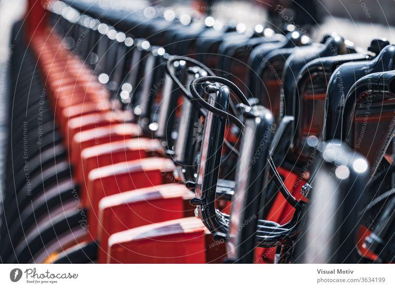 Abstraktes Detail einer Reihe moderner Mietfahrräder, die auf einer Straße der Stadt geparkt sind Fahrrad parken Miete Großstadt sonnig tagsüber urban Verkehr