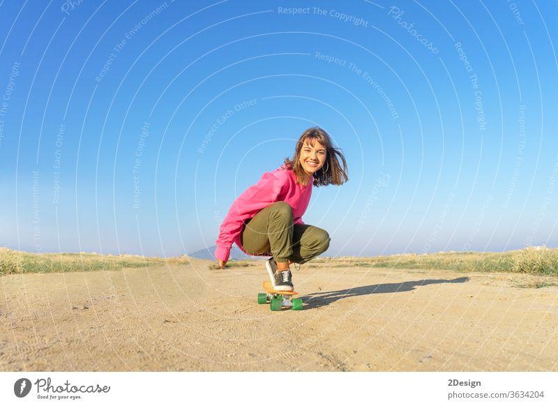 Junge Frau mit rosa Trikot, die auf einem Fußweg Skateboard fährt urban 1 Spaß jung Mädchen Mode Latein hispanisch Textfreiraum Lächeln 20s Holzplatte