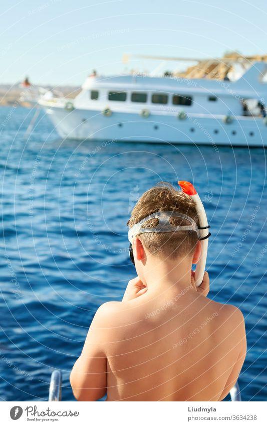 Ein Junge setzt eine Tauchermaske auf, bereit, im Meer zu schwimmen. Im Hintergrund ist eine weiße Yacht zu sehen. aktiv Strand blau Kind Konzept Korallen