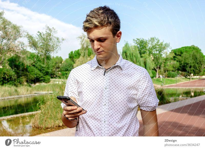 Junger blonder Mann benutzt ein Mobiltelefon im Freien männlich 1 Telefon Mobile jung Person Teenager Smartphone Typ Menschen Straße Mode Großstadt Lifestyle