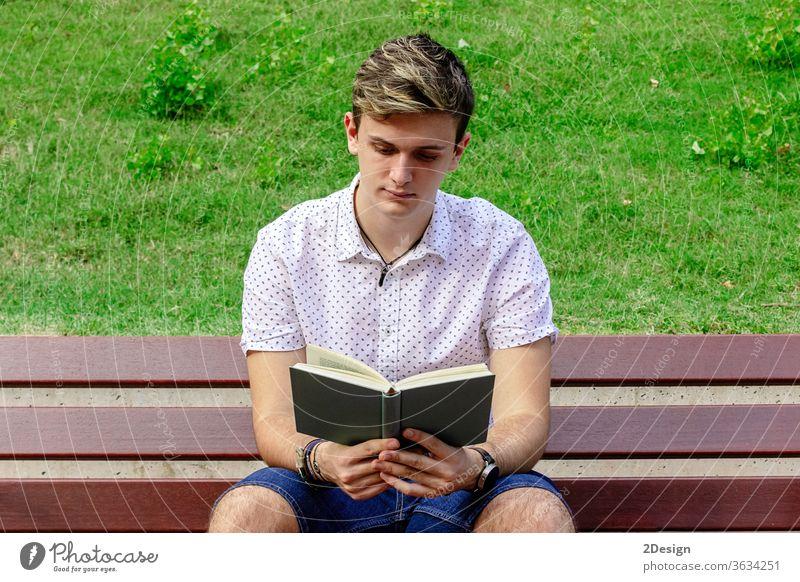 Junger Mann liest ein Buch, während er auf einer Parkbank sitzt Bank männlich jung 1 lesen photogen Erwachsener Person Sommer Schüler Kaukasier Sitzen Freizeit