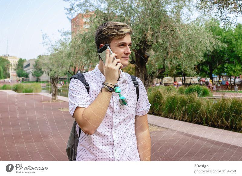 Junger Mann benutzt Mobiltelefon beim Spazierengehen im Freien Beteiligung jung 1 Glück Gesicht Person cool Freizeitkleidung Aufruf hispanisch eine Person
