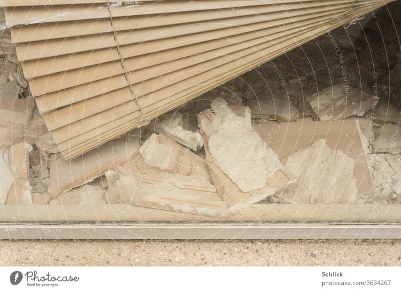 Blick in ein Schaufenster mit defekter Jalousie und Bauschutt als Detail kaputt Renovieren bankrott Steine schief schräg Insolvenz Schutt Trümmer