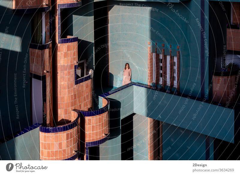 Schöne Frau mittleren Alters, die in einem modernen Gebäude an einer Wand lehnt 1 hübsch Porträt Mode Kleid lange Haare Farben mittlerer Erwachsener posierend