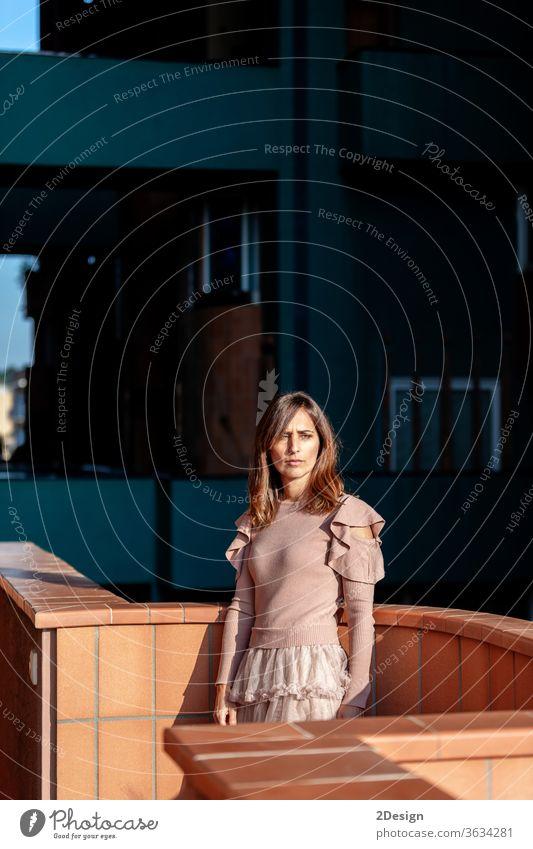 Schöne Frau mittleren Alters, die sich in einem modernen Gebäude auf den Balkon lehnt 1 hübsch Porträt Mode Kleid lange Haare Farben mittlerer Erwachsener