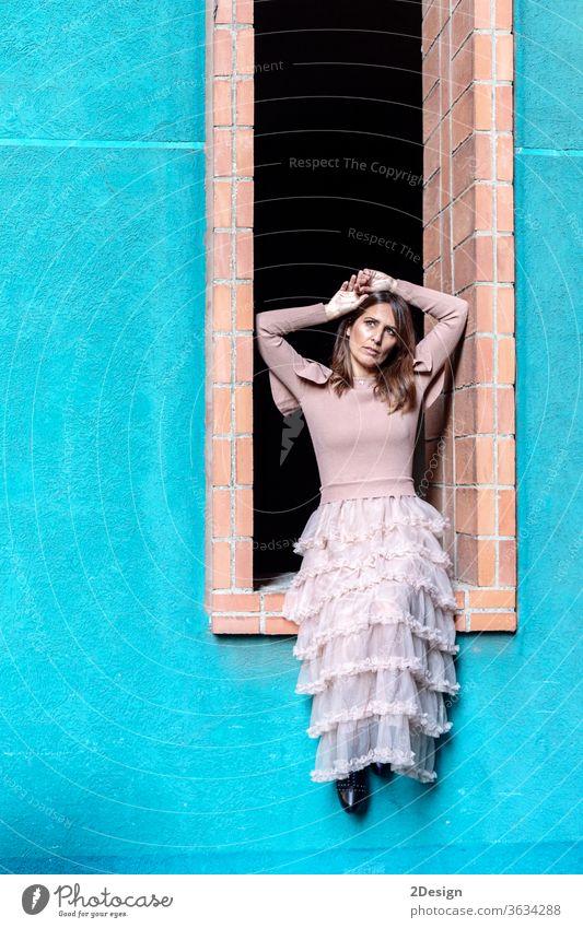 Mittelgroße, schöne Frau mit rosa Kleid, die an einem Fenster in einem modernen Gebäude sitzt 1 hübsch Porträt Mode Sitzen lange Haare Farben