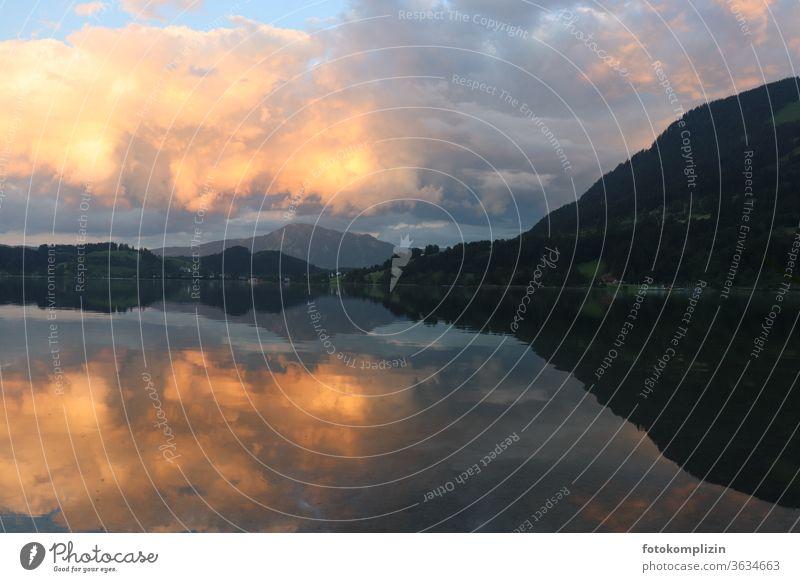 bewölkter gelber Abendhimmel an Hügelkette mit Spiegelung im See abendhimmel Dämmerung Wolken Spiegelung im Wasser Spiegelung der Wolken im See Seeufer