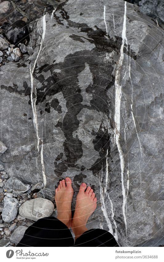 nasse Füße mit Fußabdrücken auf Felsen mit weißen parallelen Linien Flowstone Fußspuren Spurensuche Stein Steine Kieselsteine filtzen Parallelen nebeneinander