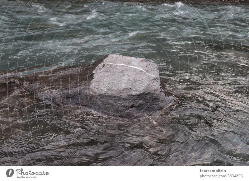 Stein mit weißem Strich im Fluss Steinblock Strichellinie Linie fließen strömen liniert Grenzstein grau Strömung Felsen Wasser Natur Bewegung Richtung Bach