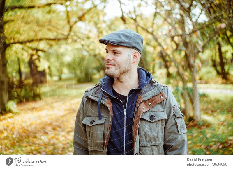 Mann, der in einem herbstlichen Wald oder Park steht. Herbst, Outdoor und Lifestyle-Konzept. Menschen Natur jung Person gutaussehend fallen männlich Porträt