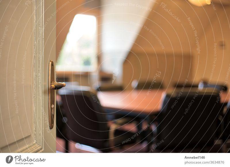 Tür mit Griff, die sich zu einem verschwommenen modernen Besprechungsraum öffnet, Hintergrund zum Bürokonzept Innenbereich Business Raum Design im Inneren Glas