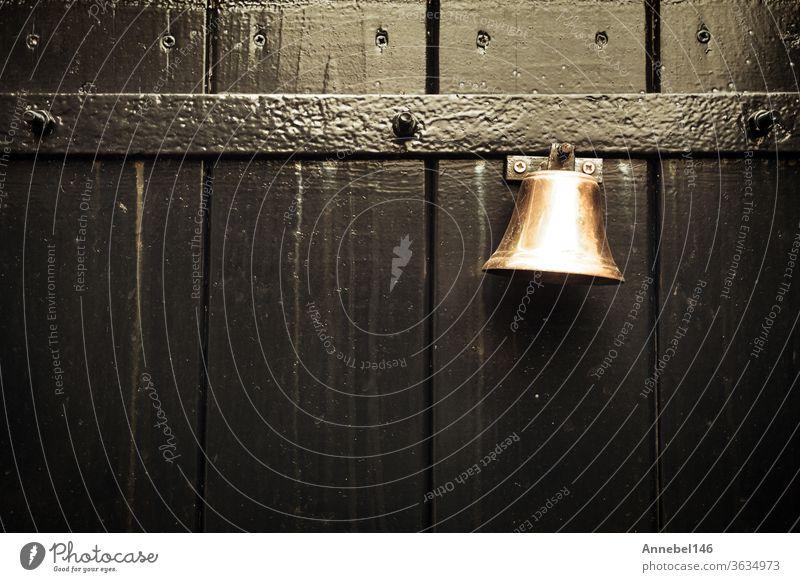 Traditionelle alte Türklingel zum Klingeln an alter Holztür, alter Hintergrundtext Architektur altehrwürdig Design Antiquität Metall retro Haus Ring Gate