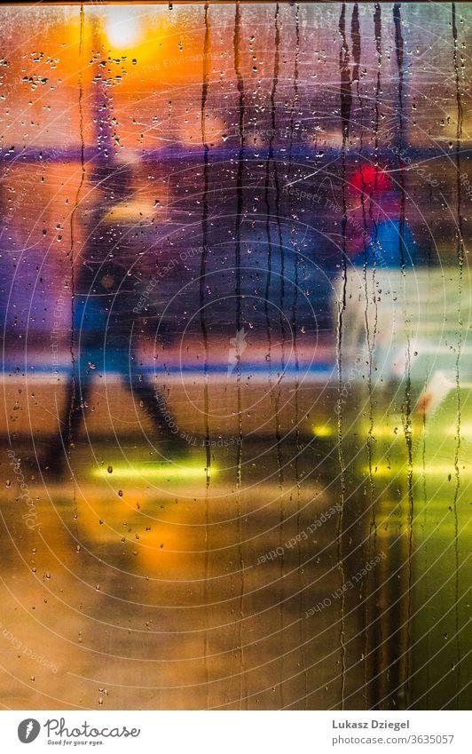 Fenster mit Regentropfen und Stadtlichtern mit einer Person im Hintergrund Nahaufnahme schließen Textur unkenntlich Silhouetten sich[Akk] bewegen
