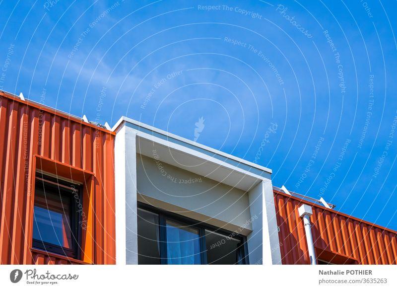 Blau-orangefarbenes modernes Gebäude mit blauem Himmel Moderne Architektur Haus Fenster Fassade Außenaufnahme Konstruktion Wohngebäude