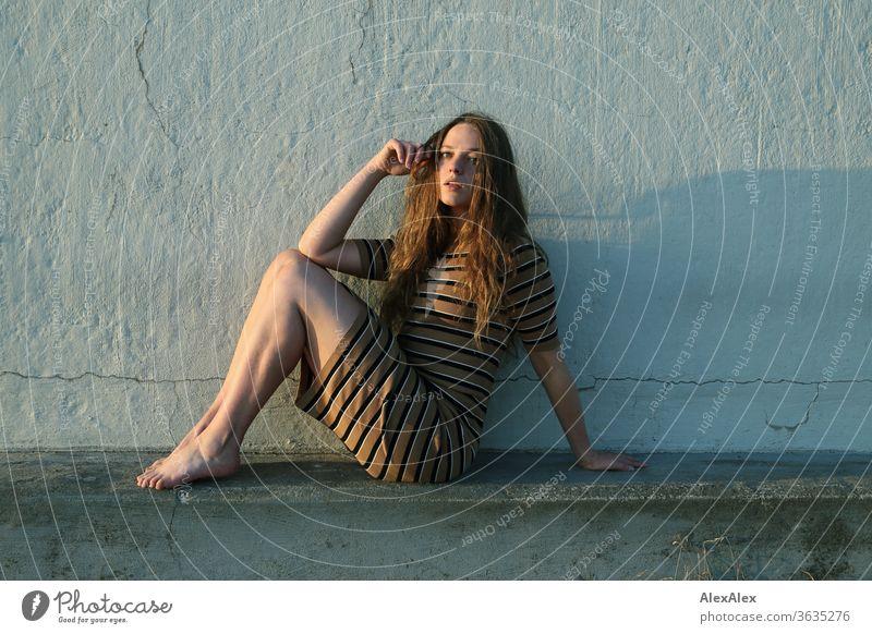 Portrait einer jungen Frau am Strand auf einer Betonmauer sitzt intensiv Mädchen Erwachsene Porträt Tag Haut Sonnenlicht selbstbewußt Zentralperspektive