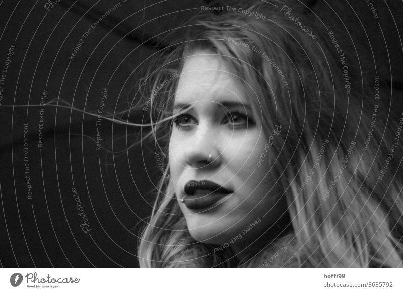 Die junge Frau bei Wind und Wetter unterm Schirm schaut in die Ferne Porträt Junge Frau Frauengesicht unscharfer Hintergrund 18-30 Jahre Erwachsene portraite